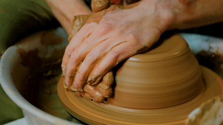 Professional male potter making bowl in pottery workshop, studio. Handmade, art and handicraft concept Stock Photo