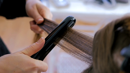 Professional hairdresser, stylist doing hairstyle and using straightener on beautiful long hair of client in white make up room. Beauty and haircare concept Foto de archivo
