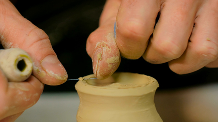 Professional male potter shaping mug with special tool in pottery workshop, studio. Crafting, artwork and handmade concept