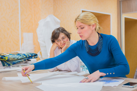 Two professional women tailors, designers discussing pattern of new couture collection at atelier, studio. Dressmaking, creativity and tailoring concept