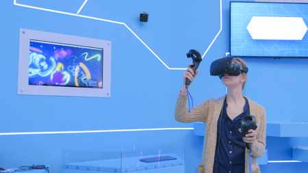 Young woman using virtual reality headset and drawing with special joystick at technology exhibition. Augmented reality and entertainment concept