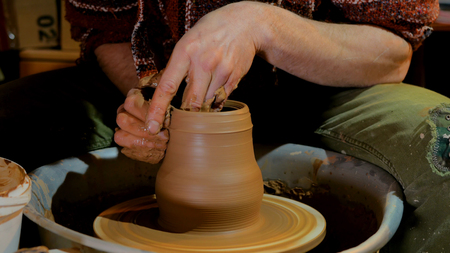 Professional male potter working with clay on potters wheel in workshop, studio. Handmade, art and handicraft concept Archivio Fotografico