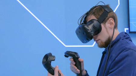Young man using virtual reality headset and drawing with special joystick at technology exhibition. Augmented reality and entertainment concept Foto de archivo
