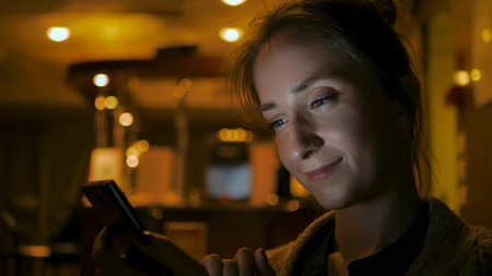 Woman using smartphone in cafe of cruise ship. Evening time, lowlight. Technology and entertainment concept