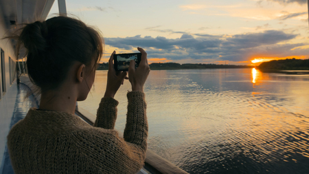 Woman silhouette taking photo of beautiful sunset with smartphone on deck of cruise ship. Sunset light, golden hour. Photography, nature and journey concept
