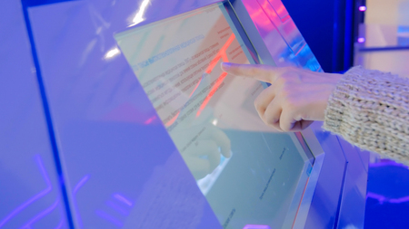 Woman using interactive touchscreen display at technology exhibition - scrolling and touching. Education and technology concept