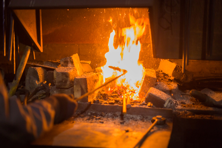 Burning fire in furnace at forge, workshop. Blacksmith equipment concept 写真素材
