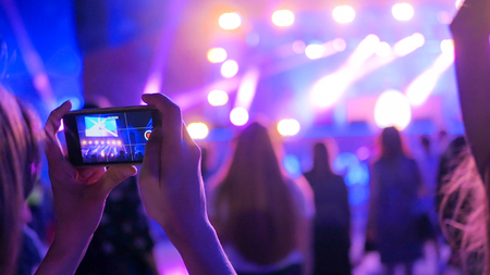 Unrecognizable woman hands silhouette taking photo or recording video of live music concert with smartphone at night. Photography, entertainment and technology concept Banque d'images - 108510913