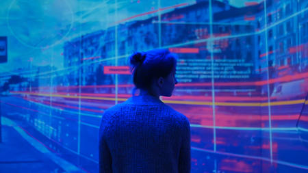 Woman looking around and watching video presentation on large display wall at futuristic technology exhibition Banco de Imagens