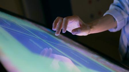Mujer con pantalla táctil interactiva en el museo moderno. Concepto de educación y tecnología