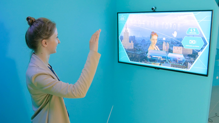 MOSCOW, RUSSIA - July 30, 2018: Smart City Exhibition. Woman taking selfie photo in front of interactive display. Leap motion and future concept