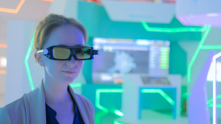 Young woman using 3d augmented reality glasses with motion sensor at technology exhibition. Futuristic background. Future and interactive concept Stock Photo