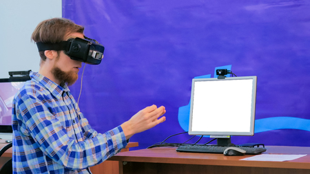 Young man using virtual reality headset in front of white blank display at technology scifi exhibition. Mockup, template, vr, sci-fi, education and technology concept 스톡 콘텐츠