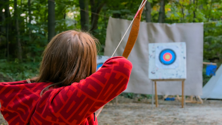 Medieval female archer shooting targets with wooden bow at historical festival. Archery and medieval culture concept 免版税图像
