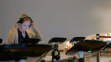 Woman using headphones and listening audio guide at modern history museum. Education and technology concept Stock Photo