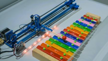 Robot playing on colorful xylophone at technology exhibition. Future and robotic concept