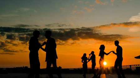 Unrecognizable people silhouette learning how to dance - on city embankment at sunset. Street dance, romantic and urban culture concept Stock Photo