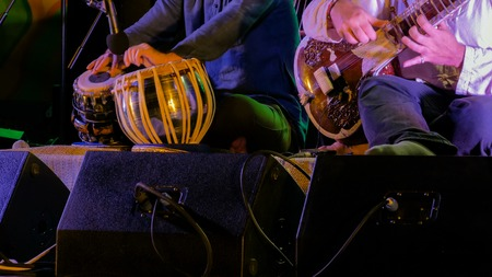 Two men playing traditional Indian tabla drums and sitar on stage of ethnic open air concert. Relaxation, meditative and traditional ethnic music concept Reklamní fotografie