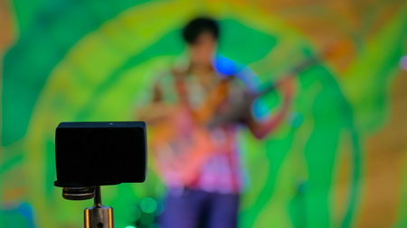 Little action video camera recording ethnic open air concert. Bass guitar player on green blurry abstract bokeh background Imagens
