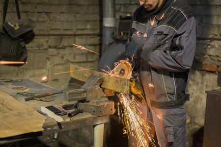 Professional blacksmith sawing metal with hand circular saw at forge, workshop. Handmade, craftsmanship and blacksmithing concept Reklamní fotografie