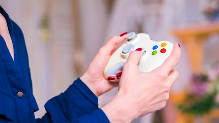 Gaming, hobby, technology and leisure time concept - woman playing video games with joystick or gamepad at home