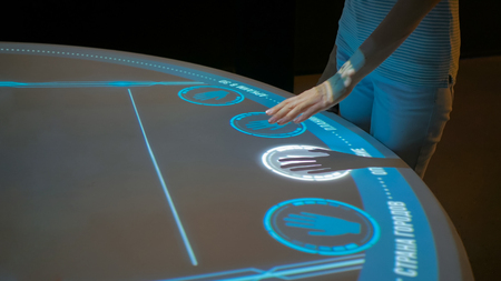 Woman using interactive display with no touch control technology at modern history museum. Education and modern concept