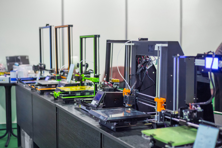 Automatic 3D printers in row during work at modern technology exhibition. 3D printing, additive technologies, 4.0 industrial revolution and futuristic concept Stock Photo