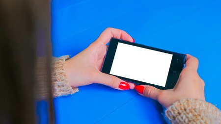 Woman looking at horizontal smartphone with white empty display. Close up shot of woman hands with mobile on blue wooden table. Technology, mock up and template concept