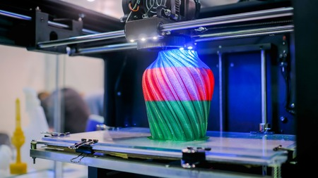 3D printer prints physical 3D model with plastic wire filament at modern technology exhibition. Additive technologies, science and futuristic concept