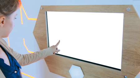 Woman using interactive touchscreen kiosk with white empty screen at modern history museum - scrolling and touching. Education, mock-up, template and technology concept