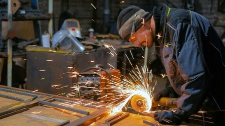 Professional blacksmith sawing metal with hand circular saw at forge, workshop. Handmade, craftsmanship and blacksmithing concept Фото со стока