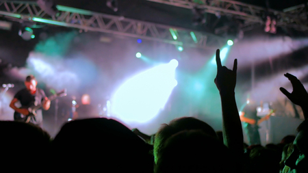 Silhouettes of people partying at rock concert in front of the stage. Entertainment and leisure concept