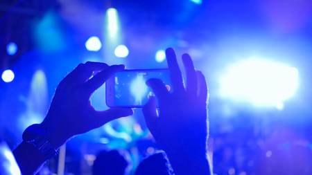 Unrecognizable hand silhouette taking photo or recording video of live music concert with smartphone. Photography, entertainment and technology concept Imagens