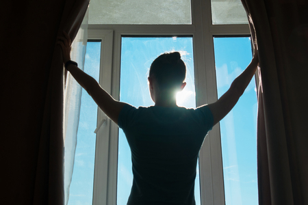 Woman silhouette opening curtains and looking out of window in hotel room at morning