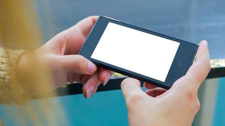 Frau, die horizontales Smartphone mit weißem leerem Bildschirm betrachtet. Schuss von Frauenhänden mit Handy hautnah. Mockup, Vorlage und Technologiekonzept