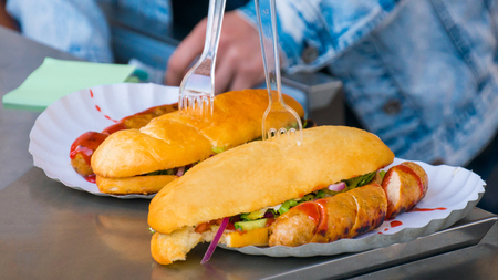 Two fresh yellow submarine sandwiches and sausages with sauce ketchup at street food festival. Outdoor cooking, gastronomy, takeaway food and service concept