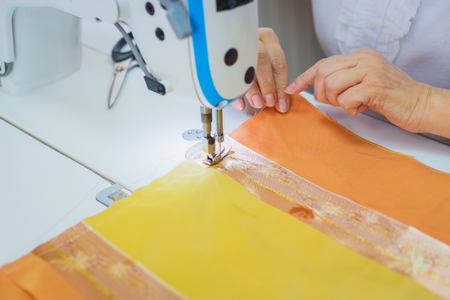 Professional tailor, fashion designer sewing clothes with sewing machine at atelier, studio. Fashion and tailoring concept