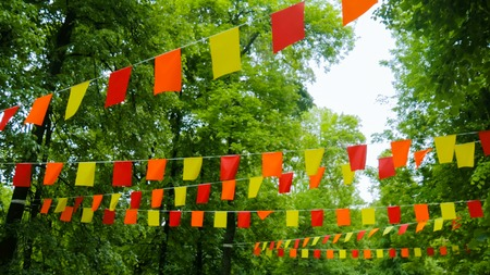 Decorative garlands of red, yellow and orange rectangular flags on street between trees Stockfoto