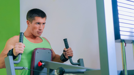 Athletic young man using exercise machine at gym, fitness club. Health, sport and workout concept