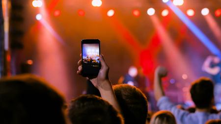 Nicht erkennbare Menschen übergeben Silhouette, die mit dem Smartphone Fotos oder Videos von Live-Musikkonzerten aufnehmen. Leute, die vor der Bühne feiern. Fotografie-, Unterhaltungs- und Technologiekonzept Standard-Bild