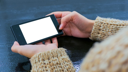 Woman using horizontal smartphone with white blank screen. Close up shot of woman hands with mobile. Mock-up, template and technology concept