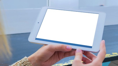 Woman looking at horizontal tablet computer with white blank screen. Mockup, template and technology concept Stok Fotoğraf