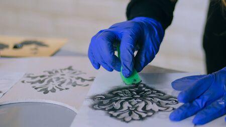 Schablonenmalerei: Nahaufnahme von Frauenhänden, die Holzkreis malen. Mal-, Hand- und Bastelarbeitskonzept