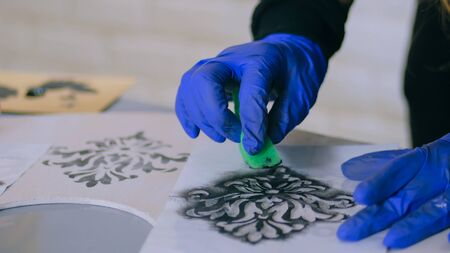 Stencil painting: immagine ravvicinata di mani di donna che dipingono un cerchio di legno. Vernice, concetto di lavoro fatto a mano e artigianale