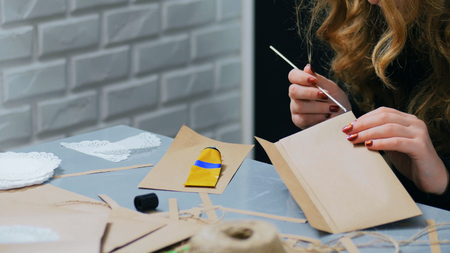 Professional woman decorator, designer working with kraft paper, applying glue and making envelope at workshop, studio - close up shot of woman hand. Design, handmade and art concept