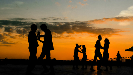 Unrecognizable people silhouette learning how to dance - on city embankment at sunset. Street dance, romantic and urban culture concept
