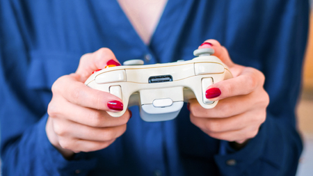 Close up shot of woman gamer hand playing video games with joystick or gamepad at home. Gaming, hobby, addiction, video game and leisure time concept Stock fotó