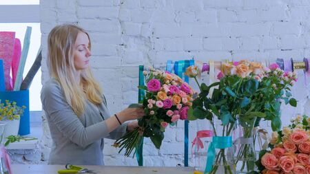 Professional woman floral artist, florist making beautiful bouquet of colorful roses at workshop, flower shop. Floristry, handmade and small business concept