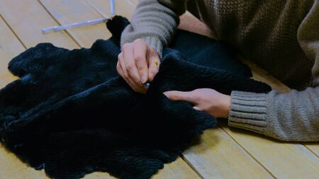 Professional male skinner, furrier working with beaver fur skin at atelier, workshop. Fashion and leatherwork concept Stock fotó