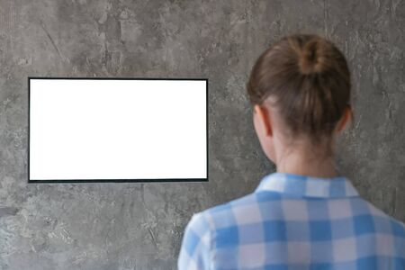 Mockup image - woman watching flat smart led TV with white blank screen hanging on wall in the living room at home. Mock up, copyspace, leisure time, template, entertainment and technology concept